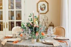 一把餐桌和舒适的扶手椅子在有一个轻的餐厅的一个现代房子里 图库摄影