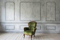 一把经典扶手椅子对一个空白墙壁和楼层 复制空间 库存图片