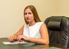 一把黑扶手椅子的女孩 免版税库存照片