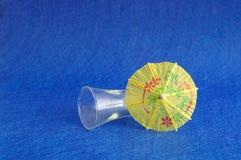 一把黄色鸡尾酒伞显示与一块空的射击者玻璃 免版税库存照片