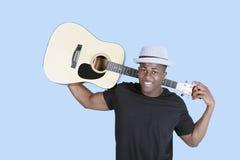 一把年轻非裔美国人的人运载的吉他的画象在浅兰的背景的 免版税库存照片