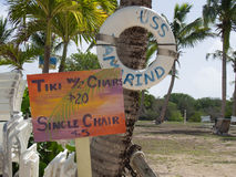 一把Tiki和椅子的价格的五颜六色的标志在海滩 免版税图库摄影