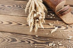 一捆绑麦子和鸦片和全部疏散五谷和一半与面包片的面包在老木板条的 库存图片