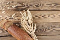 一捆绑麦子和鸦片和全部疏散五谷和一半与面包片的面包在老木板条的 图库摄影