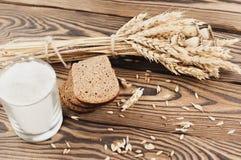 一捆绑麦子和鸦片和全部疏散五谷和三片面包片和面粉在玻璃在老木板条 库存照片