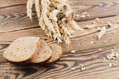 一捆绑麦子和鸦片和全部疏散五谷和三片面包片在老木板条的 免版税库存照片