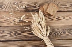 一捆绑麦子和鸦片和全部疏散五谷和三片面包片在老木板条的 库存图片
