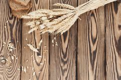 一捆绑麦子和鸦片和全部疏散五谷和三片面包片在老木板条的 免版税库存图片