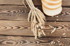 一捆绑麦子和鸦片和全部疏散五谷和面包片在老木板条的 免版税库存图片