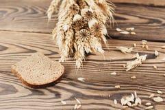 一捆绑麦子和鸦片和全部疏散五谷和面包片在老木板条的 库存图片