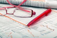 一支圆珠笔和放大镜在报纸 免版税库存图片