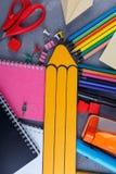 一支大黄色纸铅笔,在品种旁边书写,笔记本、钳位和蜡笔和其他办公用品 免版税库存图片
