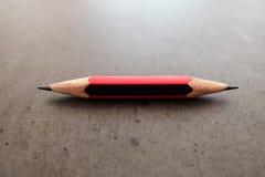 一支小铅笔, shapened在两个末端,在一张灰色桌上 免版税库存照片