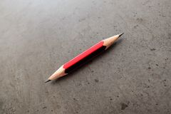 一支小铅笔, shapened在两个末端,在一张灰色桌上 免版税库存图片