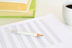 一支笔和音乐纸张在有些书和一杯咖啡旁边在一张书桌上在教室 空的拷贝空间 免版税库存图片