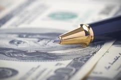 一支笔的特写镜头在金钱的 免版税库存照片