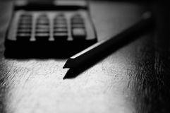 一支计算器和铅笔在书桌上 免版税库存照片