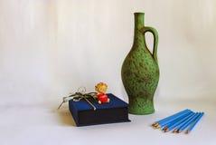 一支铅笔、一个水罐和一个天使在白色 库存图片