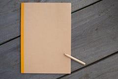 一支铅笔与回收在木头的笔记本 免版税图库摄影
