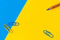 一支铅笔和三个纸夹反对一蓝色和黄色backgrou 免版税库存照片