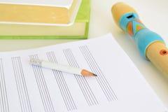 一支长笛、一支铅笔和音乐纸张在有些书旁边在一张书桌上在教室 空的拷贝空间 免版税库存图片
