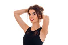 一支黑礼服和红色唇膏的性感的女孩在嘴唇保留手头发并且调查照相机 库存照片