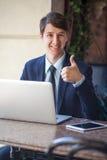 一放松了年轻英俊的专业商人与他的膝上型计算机、电话和片剂一起使用在一个喧闹的咖啡馆 免版税图库摄影