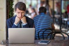 一放松了年轻英俊的专业商人与他的膝上型计算机、电话和片剂一起使用在一个喧闹的咖啡馆 免版税库存图片