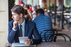 一放松了年轻英俊的专业商人与他的膝上型计算机、电话和片剂一起使用在一个喧闹的咖啡馆 库存照片