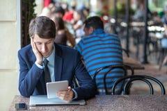一放松了年轻英俊的专业商人与他的膝上型计算机、电话和片剂一起使用在一个喧闹的咖啡馆 图库摄影