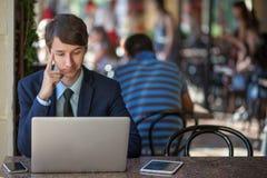 一放松了年轻英俊的专业商人与他的膝上型计算机、电话和片剂一起使用在一个喧闹的咖啡馆 免版税库存照片