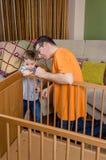 一新出生的父亲和儿子聚集的轻便小床在 免版税库存图片