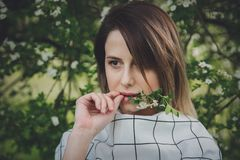 一方格dressstay的年轻女人在开花的树附近 库存照片