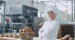 一时髦制服微笑的美丽和吸引人妇女面包师大在大面包店产业的照相机前面 股票视频