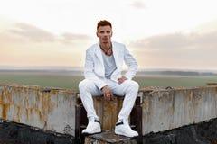 一时髦白色衣裳坐的年轻英俊的人 库存照片