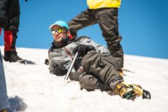 一晴朗的斑点和专业设备说谎的基于的一名登山家他的同志围拢的一个多雪的倾斜 免版税图库摄影