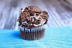一曲奇饼和奶油色杯形蛋糕在蓝色立场木背景 免版税库存图片