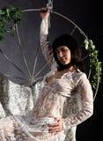 一有花边的peignoir的性感的高雅女孩,摇摆在金属摇摆 金属棒的举行 免版税库存图片