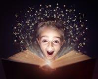 读一本不可思议的故事书的孩子 免版税库存照片