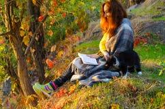 读一本书在秋天公园和宠爱fluf的少妇 免版税库存图片