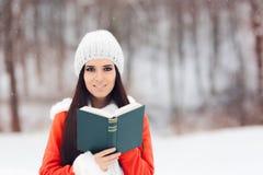 读一本书外面在雪的冬天妇女 免版税库存照片