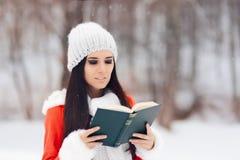 读一本书外面在雪的冬天妇女 库存照片