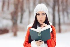 读一本书外面在雪的惊奇的妇女 库存照片