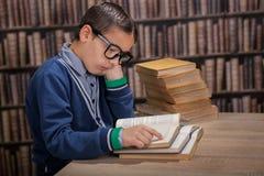 读一本书的一个年轻天才在图书馆里 库存图片