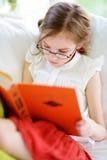 读一本书的可爱的小女孩佩带的镜片在白色客厅在夏日 免版税库存照片