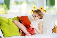 读一本书的可爱的小女孩佩带的镜片在白色客厅在夏日 图库摄影