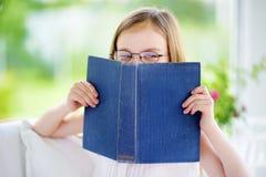 读一本书的可爱的小女孩佩带的镜片在白色客厅在夏日 库存照片