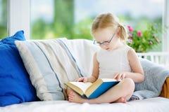 读一本书的可爱的小女孩佩带的镜片在白色客厅 图库摄影