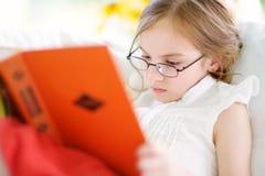 读一本书的可爱的小女孩佩带的镜片在白色客厅 免版税库存图片