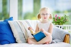 读一本书的可爱的小女孩佩带的镜片在白色客厅 库存图片